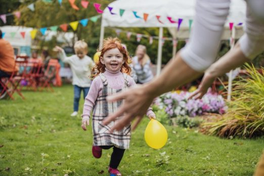 Two young children enjoy playing with balloons at a garden party,