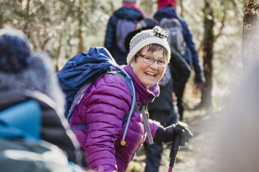 Member of a fundraising group smiles at the camera during a hike