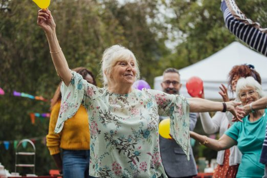 A senior female enjoys dancing in the garden at an autumn tea party. Adults dance around her and colourful bunting and balloons decorate the garden.