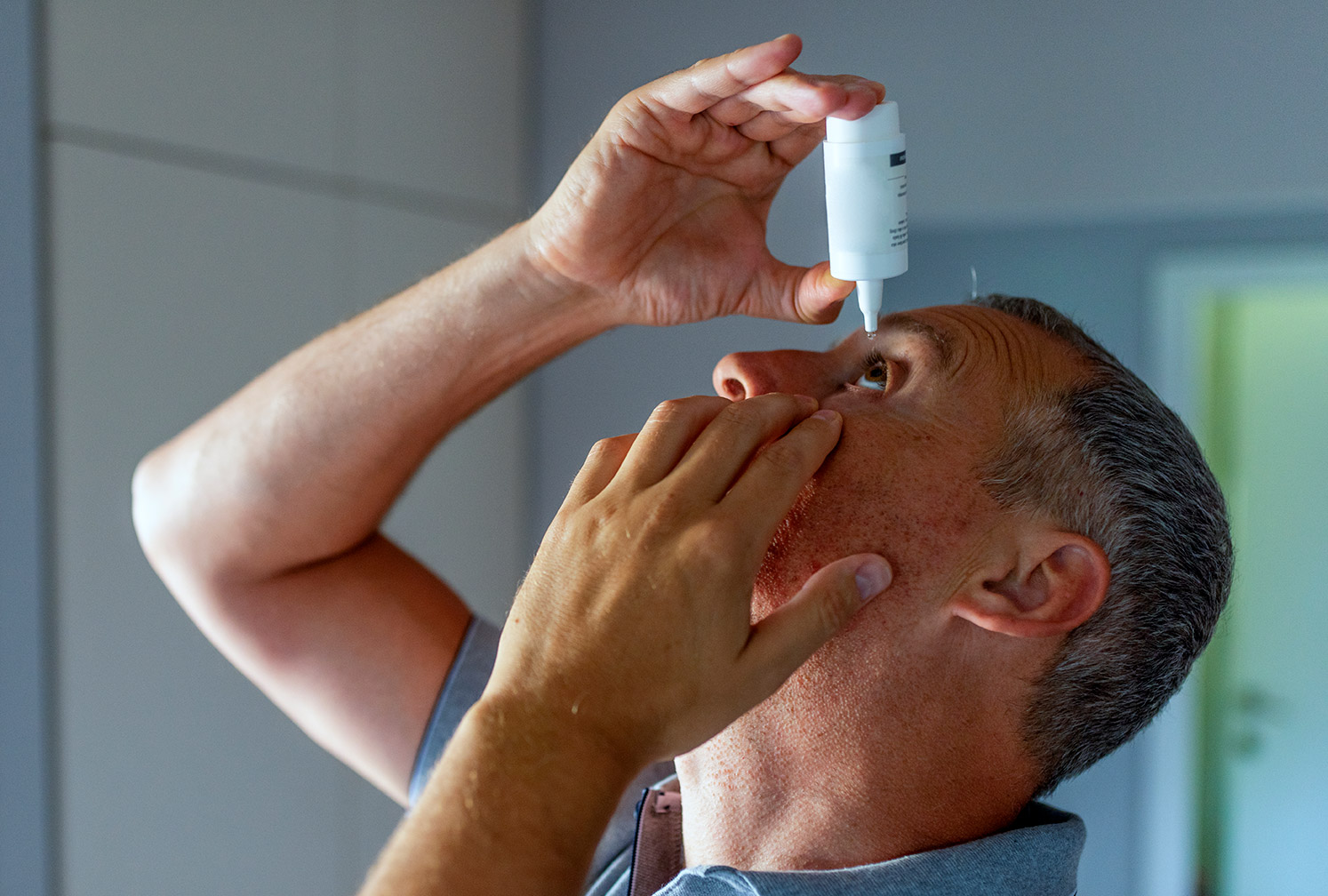 A man putting in eye drops
