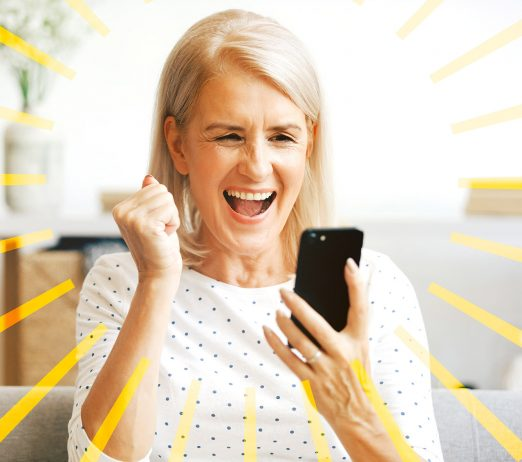 A woman looking excitedly at her phone and cheering