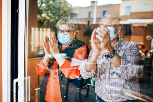 older couple wearing medical masks clapping at a window