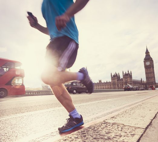 Person running with Big Ben and a london bus in background